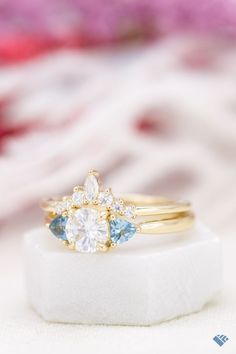 A sparkling beauty of an engagement ring... wearing the tiara it deserves. Two perfect pops of aquamarine to offset all the surrounding sparkle. Crown Engagement Ring, Classic Engagement Rings, Designer Engagement Rings, Tiara Ring, Tiaras And Crowns, Bridal Sets, Her Style, Ring Designs, Halo