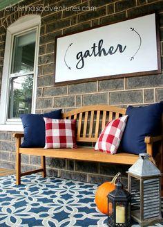 This fall front porch features a monogram pumpkin, mums, hay bale, pumpkins…