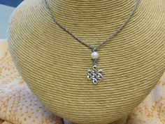 Sterling Silver Love Knot Necklace With Pearl...strung on tiny cotton cord...very durable for all the time wear.