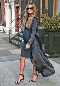 Chrissy Teigen Glowing In Gray-Mom-to-be Chrissy Teigen stepped out in style in New York City on Tuesday (March 1). While heading to Live! with Kelly and Michael, the FABLife star, 30, was glowing in a gray maternity midi dress paired with a long coat and strappy heels.