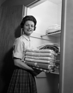 housewife holding laundry folded towels by linen closet looking at camera. (This reminds me S.