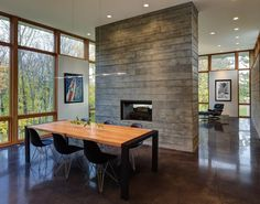 This house features a central concrete fireplace, surrounded by polished concrete floors. Fieldstone House by Bruns Architecture