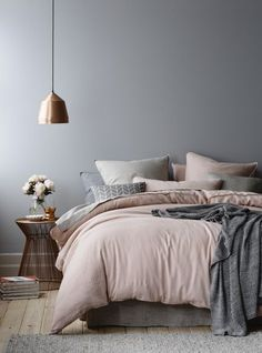 Urban glam design, with headboard-less bed (looks like mattress floating on platform) with thin, gilded end table and copper tone hanging lamp.