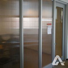 When used as an interior wall, polycarbonate panels provide natural light and privacy for room occupants. Polycarbonate Panels, Commercial Interiors, Interior Walls, The Office, Hearth, Natural Light, Divider, Agra, Glass Doors