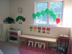 Montessori inspired playroom- simple shelves at left hold this week's favorite activities for easy access & cleanup, kitchen counter workspace = easy cleaning.  simple art = easily changed above counter. visually clean, lower stimulation environment = helps kids focus where they want & relax