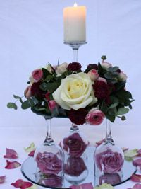 a centerpiece which combines wedding flowers and a candle