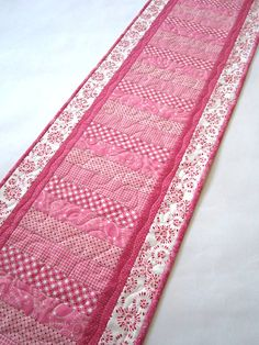 Quilted Table Runner Valentines Day 14 x 49 A pink table runner for Valentines Day or use all year on a dresser. This runner has a a variety of pinks in the fabrics. A great piece to display with all your other Valentine decorations. Give this table runner as a gift.  This table runner is 14 x 49 . The fabric is made with 100% cotton. Warm 100 from Warm Company was used for the batting. I used an pink colored cotton thread and quilted a variety of stitches in this table runner. The binding…