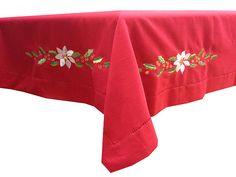 Mantel navideño rojo con ramos de hojas de acebo bordadas en el centro y la caida del mantel.  El dobladillo rematado con una vainica. Consulte precio y medidas en http://tienda.lagarterana.com/