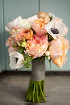 The bridesmaids will carry round bouquets of coral peonies, peachy orange ranunculus, and anemones and sage leaves wrapped in a soft gold with the stems showing.