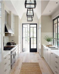 Perfect galley kitchen. Light floors, counters and cabinets with black door, windows and light fixtures