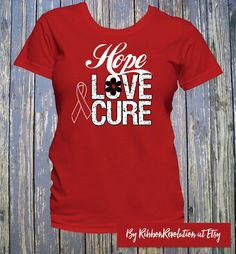Hope Love Cure shirts with an outline ribbon signifies awareness for AIDS, Blood Cancer, Heart Disease, HIV, Stroke and Vasculitis Awareness. Design features distressed and scripted style text with an outline ribbon to highlight the color of the shirt.