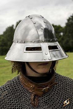 """Die Optik des Wächter Helms ist auf mittelalterliche Originalfundstücke zurückzuführen. Charakteristisch ist vorallem die breite """"Krempe"""" des Helms, welche für viel Bewegunsfreiheit des Trägers sorgt. Der Helm wird mit einem brauen Lederband verschlossen, welches an der Schnalle mit einem weichen Lederpad versehen ist um vor Scheuerungen zu schützen.  Herstellerhinweis: Um Rost zu vermeiden, sollten die Metallteile trocken gelagert und eingeölt werden.  Verfügbare Größen: M, L Maße (ohne…"""