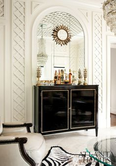 white lattice walls and a black + brass lined lacquer cabinet