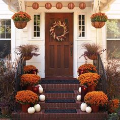 Thanksgiving front door decorated with mums and white pumpkins.