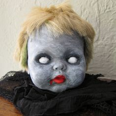 diy Zombie Baby Head by katbaro, using old dolls... funny thing is.. the 'cute' doll is JUST as CREEPY to me as the zombie doll head hahhaha