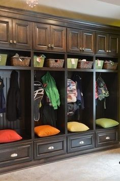 Just inside the front door with a spot for each family member, their raincoat, gumboots, coat, hat, schoolbag etc. Make the bottom drawer bigger though so you can store shoes in it