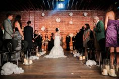 Modern White Loft Wedding - Aisle lined with alternating clusters of large glass cylinders with wax LED pillar candles, petals and white poufs, which are also hung with crystals for the alter | Floral Designer: Andrea Layne Floral Design | Venue: Nova 535 | Photography: Life Long Studios