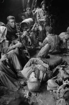 U.S. soldiers of the 9th Infantry Division relax on the long boat trip back to their base camp after a day trudging through the coconut groves of Kien Hoa province in the Mekong Delta/January 1969.