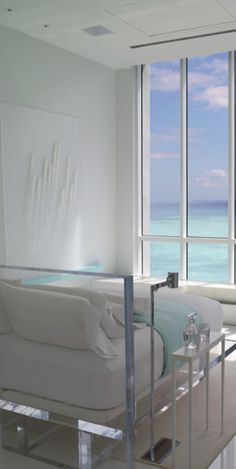 Modern Bedroom with an Ocean View. The plexiglass bed frame is pretty cool.