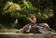 Boy catching a fish in Indonesia