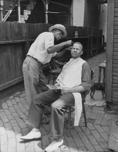 A traveling barber cutting a man's hair in a bricked-over backyard. Photograph by Alfred Eisenstaedt. Homestead, Pennsylvania, July 1936.
