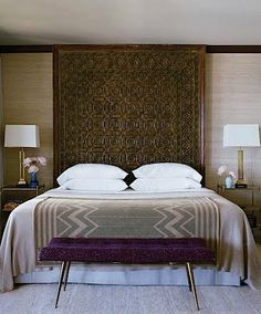 Master bedroom with carved wood as headboard, up to ceiling. Nice.