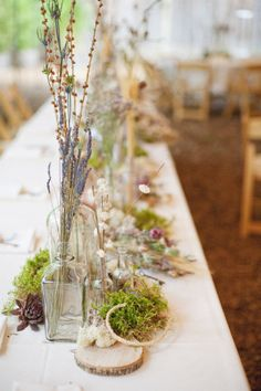 woodsy table setting - dried lavender, vintage inspired bottles, dried moss, wood block, dried flowers.