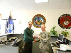 """GM Emilio Montanez of Omni's Junction City. KS office proudly hands SFC Nicholas Wiley a supply of $15.00 turkey certificates to hand out to members of his Unit that need a little assistance during the holidays. This is a Win-Win program for all concerned. """"Holiday Giving"""" will continue in December as Omni will be handing out $15.00 ham certificates prior to Christmas as our way of saying """"Thank You"""" to the soldiers of FT Riley."""