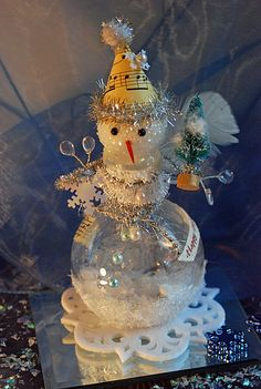This delightful snowman is just full of tinsel and cheer. The head is made of styrofoam with a splash of glitter. His hat is made out of a piece of