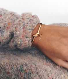 pastel/neutral sweater and gold accessories