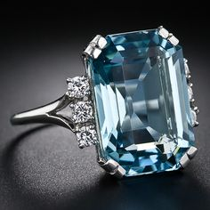 A richly saturated emerald-cut aquamarine weighs about 12.40 carats (but presents considerably larger due to masterful lapidary work), is embellished on each side by a sparkling trio of round brilliant-cut diamonds in this superb and impressive bauble, handcrafted in platinum, circa 1960s-1970s. A cool and refreshing swimming pool for your finger! The aqua measures 15/16 inch long by 1/2 inch wide. Lang Antiques.