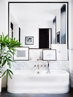 Modern bathroom space with a floating tub, an indoor plant and artwork