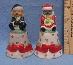 2 Ceramic Christmas Bells, one has a Cat, and the other has a Dog sitting on top of the bell. So cute!