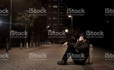 Traurige Frau sitzt auf dem Boden auf Straße am Abend alleine ein deprimierter Lizenzfreies stock-foto
