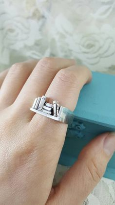 This silver bookshelf ring is the bomb; and its even cooler in person. The back of the band is slightly squared to keep the top of the design from spinning around during wear.
