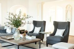 Stunning living room features a pair of gray wingback chairs flanking iron and…