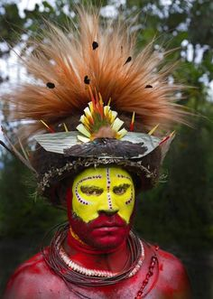 A Huli wigman at the Paiya Show sing-sing wearing a head-dress with superb bird of paradise breast shield, Papuan lorikeet feathers and plumes from raggiana bird of paradise and Lawes parotia. tribal face paint rainforest - Google Search