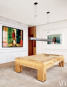 Eran Chen of ODA Architecture devised the layout of this expansive family residence in New York City. A billiard table and ceiling lamp anchor the lounge, where a Yigal Ozeri painting (right) hangs against a Weitzner wall covering.