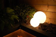 Glowing Outdoor Orbs: You need opaque glass shades, & christmas lights: Just stick the glass shades anywhere you want & stuff them full of mini lights. Attach an extension cord if you need to & hide it under your garden dirt or mulch. I have my lights on a timer so they come on every night at dusk.