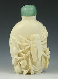 Chinese carved ivory snuff bottle. The ivory bottle is well carved with a large beetle or other insect perched on a vine of berries and leaves at the center.