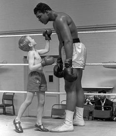 Cassius Clay (Muhammed Ali) with 6 years old Patrick Power in the ring during his training for the Heavyweight title fight against Henry Cooper, June 1963. °