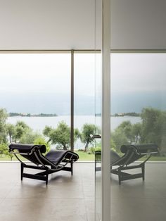 The villa is designed to live in symbiosis with nature without any separation. Two volumes of glass between the slope and the water of the lake surrounded by open spaces covered with white stone and wood that are creating a play of light and shadow with the large frameless sliding Sky-Frame windows that give way to the majestic panorama and outdoor life in the beautiful park creating a unique environment that blends with the outside.  Photography: Marcello Mariana Beautiful Park, Open Spaces, White Stone, Light And Shadow, Outdoor Life, Outdoor Furniture, Outdoor Decor, Sun Lounger, Environment