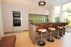 Cashmere handleless kitchen in a satin lacquer kitchen finish. The kitchen island is finished in a Platinum Oak Veneer.