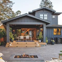 Our Los Gatos Idea House makes one notable departure from traditional craftsman homes—it doesn't have a formal dining room. That's where the large covered patio comes into play—the long dining table gives the homeowners a truly Californian space to entertain. Folding glass doors create a seamless flow between inside and out, and skylights illuminate the warm, cedar-lined porch.    Fire pit and pavers: @belgardoutdoorliving  Folding doors: @lacantinadoors  Decking: @azekbuildingproducts