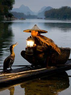 Fisherman with his cormorant partner
