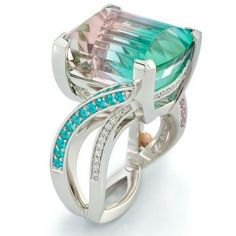 The star of this gorgeous @coffinandtrout ring is a rare 17.76ct Tri-Color Tourmaline. The Tourmaline displays pink, blue and green colors which are complimented perfectly on the sides by glowing Paraiba Tourmalines and pastel Pink Sapphires. Flowing diamond accents finish off this Platinum masterpiece.