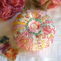 I ❤ pincushions . . . Shabby Chic Patchwork with Sweet Flower Fabrics Pincushion- An emery pocket gives this pincushion a solid feel while new polyester fiberfill gives it softness. Emery is also a great needle and pin sharpener. Pretty pearly pink buttons and a vintage crochet rose add the perfect finishing touch. This generous cushion is 5 inches across and 2 inches plump. ~By Fiberluscious