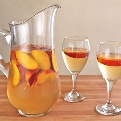 Place the sliced peaches into the bottom of the sangria pitcher.