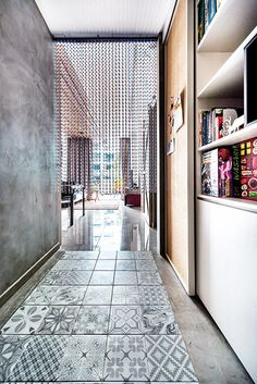 """The foyer, which features concrete screed surfaces, graphic tiles and a colourful assortment of board games, sets the tone for the homeowner """"play den"""" beyond. Bathroom Styling, Bathroom Interior Design, Bathroom Floor Tiles, Tile Floor, Home Design, Wicker Dining Chairs, Diy Home, Home Decor, Inspiration Design"""