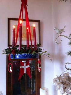 Advent candles hanging from the ceilng. Danish Christmas ornaments and a danish flag are attached to it too.